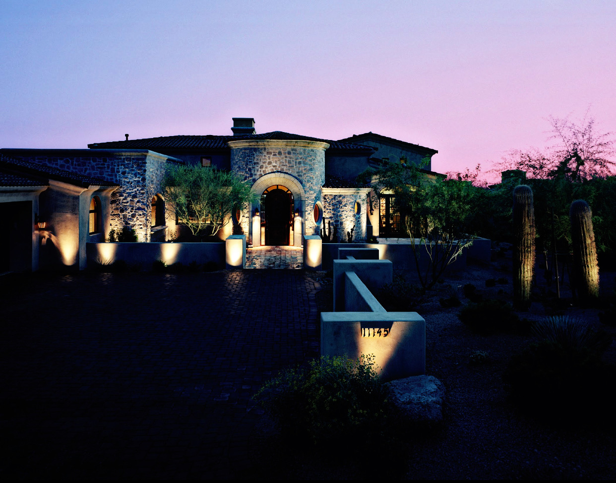 Residential landscape lighting surrounding large home at dusk