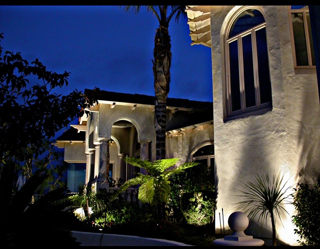 Residential landscape lighting along perimeter of large home at night