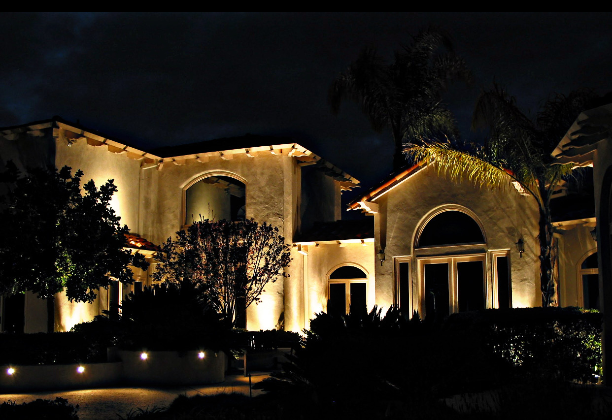 Residential landscape lighting on large home at night