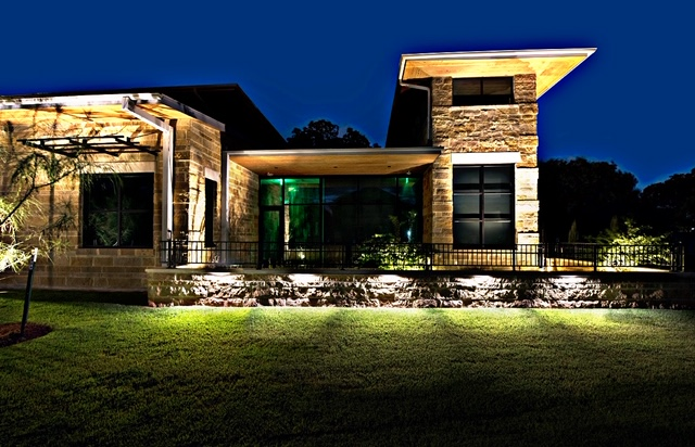 Residential landscape lighting surrounding large home at night